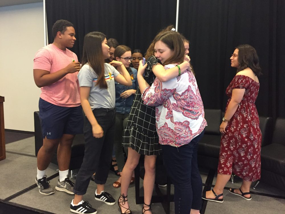 Madie Lake, an organizer with the Houston March for Our Lives group, hugs a student from Santa Fe High School at a press conference Friday.