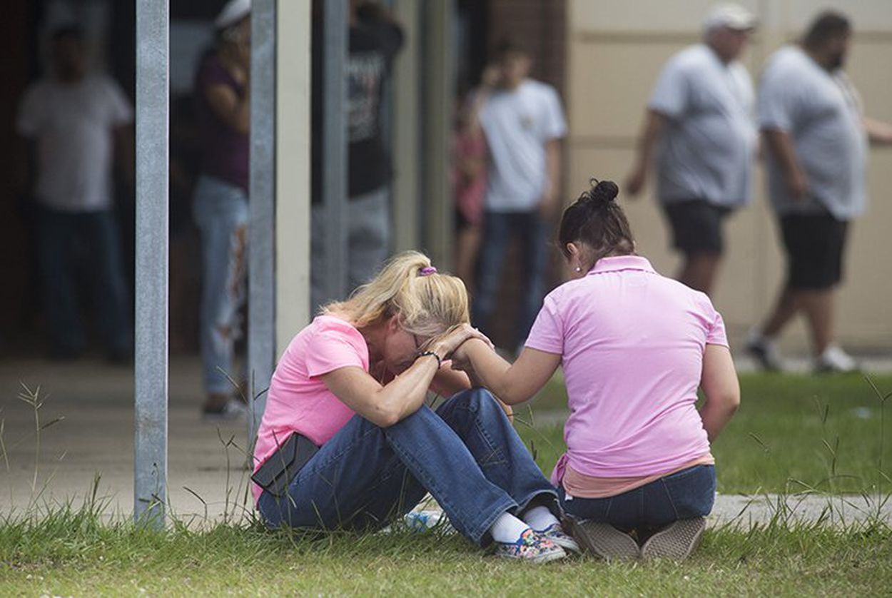People outside a middle school set up as a reunion point for parents and students in Santa Fe, Texas on Friday, March 18, 2018 after a gunman killed at least 10 people at Santa Fe High School.