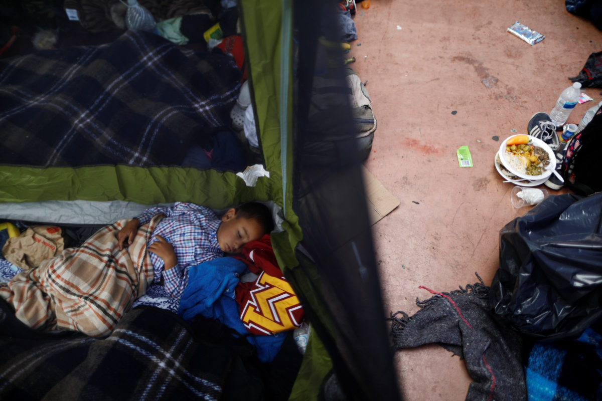 A child traveling with a caravan of migrants from Central America sleeps at a camp near the San Ysidro checkpoint, after U.S. border authorities allowed the first small group of women and children entry from Mexico overnight, in Tijuana, Mexico.