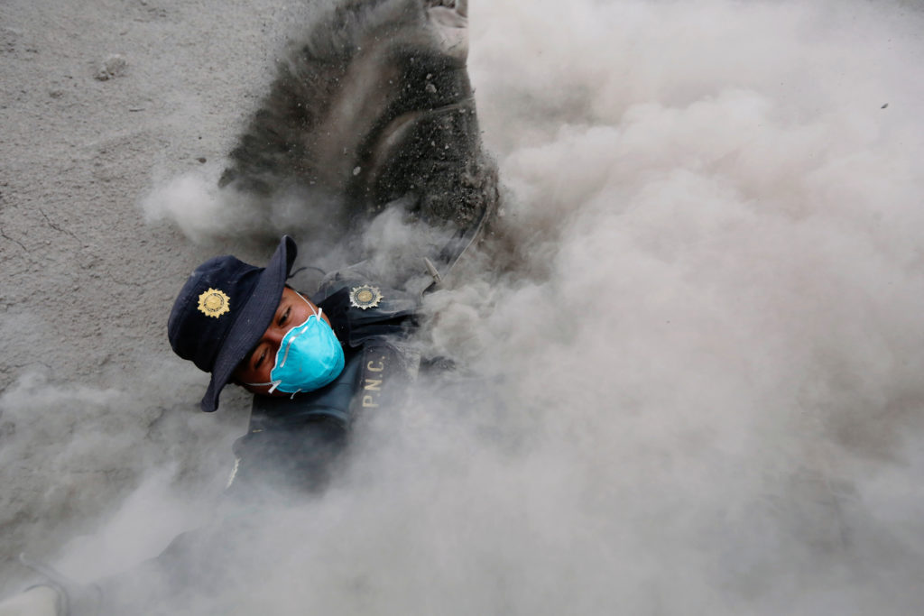 A police officer stumbles while running away from a new pyroclastic flow spewed by the Fuego volcano in the community of San Miguel Los Lotes in Escuintla, Guatemala, June 4, 2018.