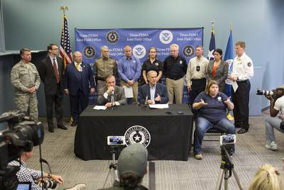 Gov. Greg Abbott, Texas A&M Chancellor John Sharp (head of the Governor's Commission to Rebuild Texas) and leaders of several state agencies give an update on Harvey recovery efforts at the FEMA Joint Field Office in Austin on Sept. 14, 2017.