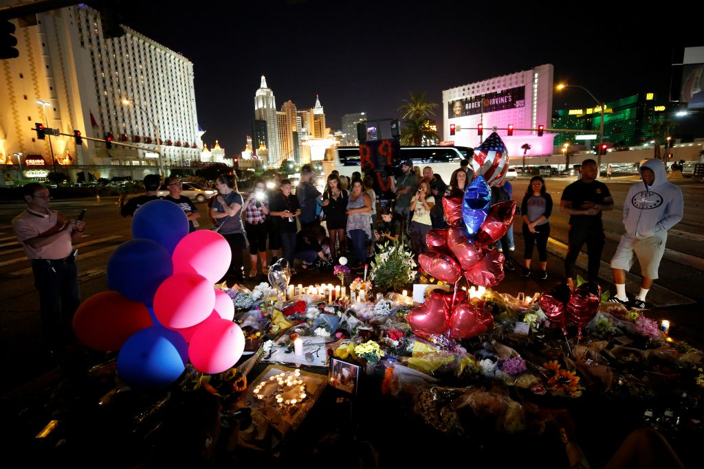 People gather at a makeshift memorial in the middle of Las Vegas Boulevard following the mass shooting in Las Vegas, Nevada.