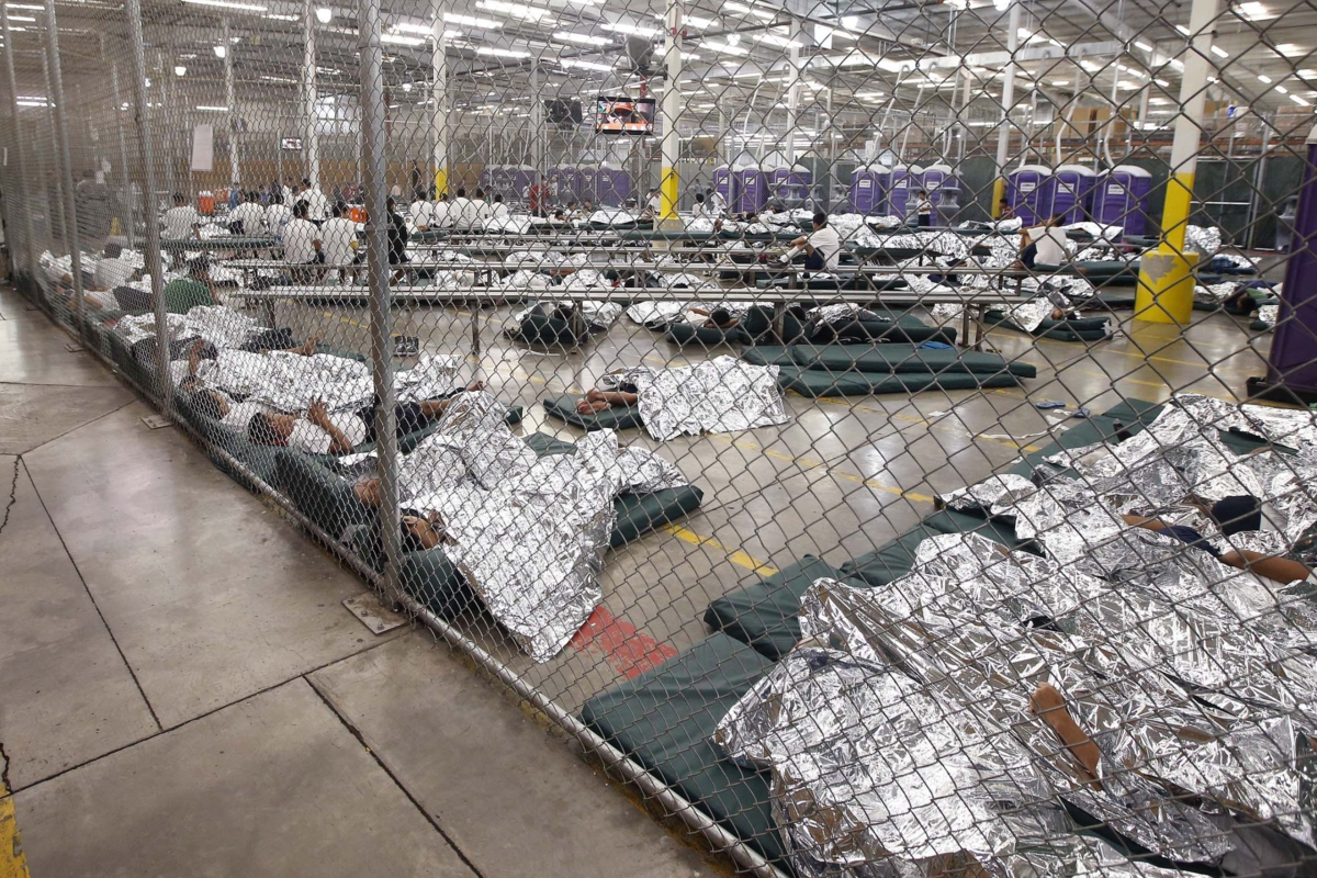 Detainees sleep and watch television in a holding cell where hundreds of mostly Central American immigrant children are being processed and held at the U.S. Customs and Border Protection Nogales Placement Center in Nogales, Ariz. in this June 18, 2014, file photo.