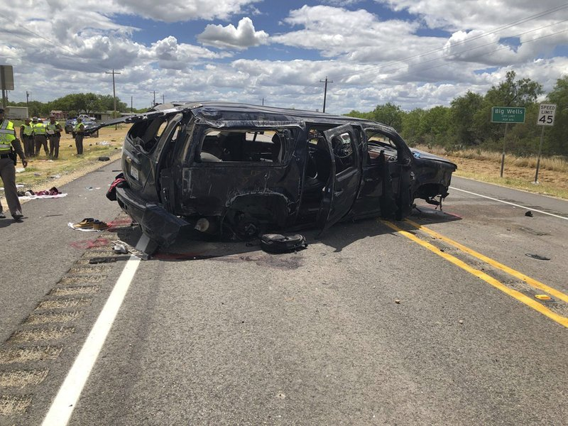 In this image tweeted by David Caltabiano of KABB/WOAI, a heavily damaged SUV is seen on Texas Highway 85 in Big Wells, Texas, after crashing while carrying more than a dozen people fleeing from Border Patrol agents, Sunday, June 17, 2018.