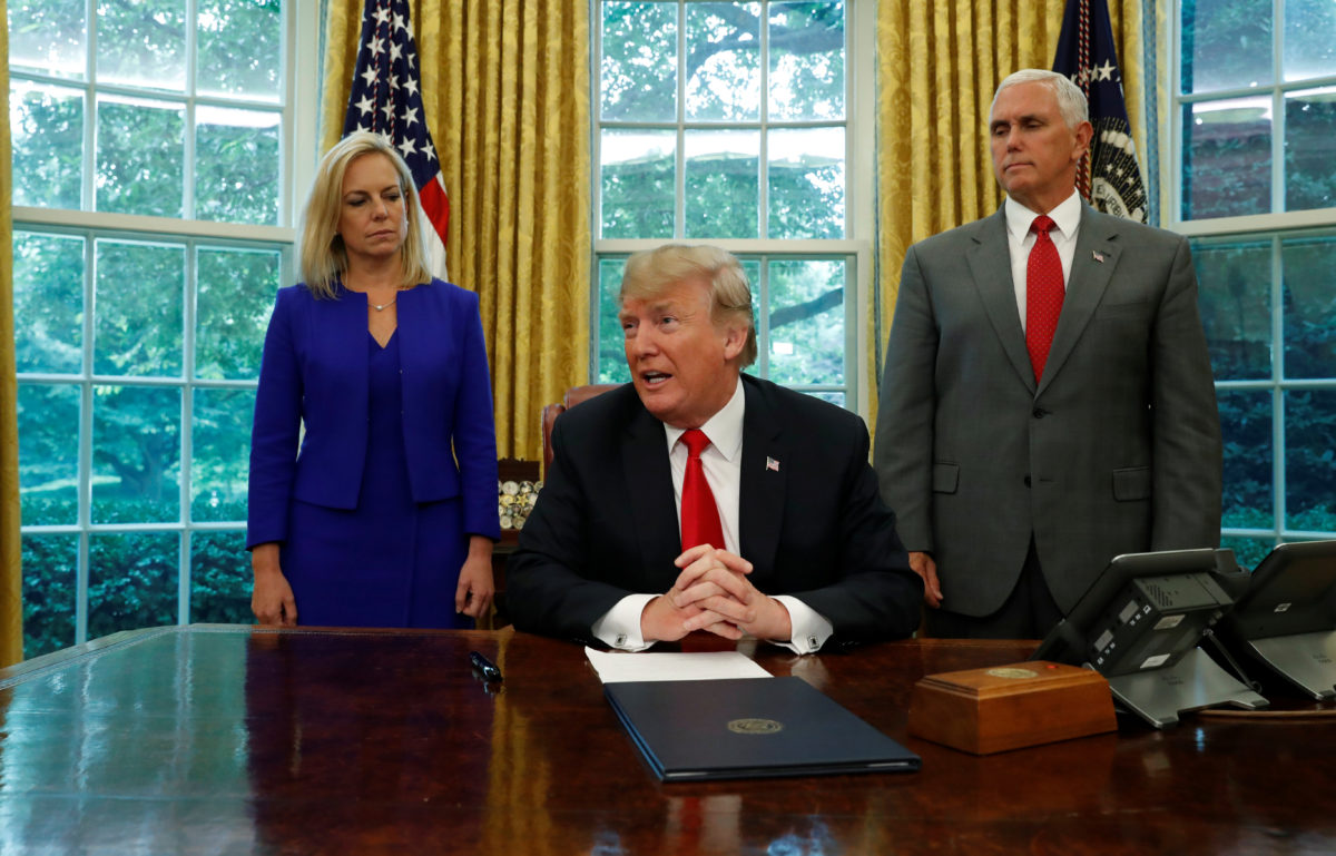 President Donald Trump sits at this desk in the Oval Office with DHS Secretary Kristin Nielsen and Vice President Mike Pence prior to signing an executive order on immigration policy at the White House in Washington, U.S., June 20, 2018.