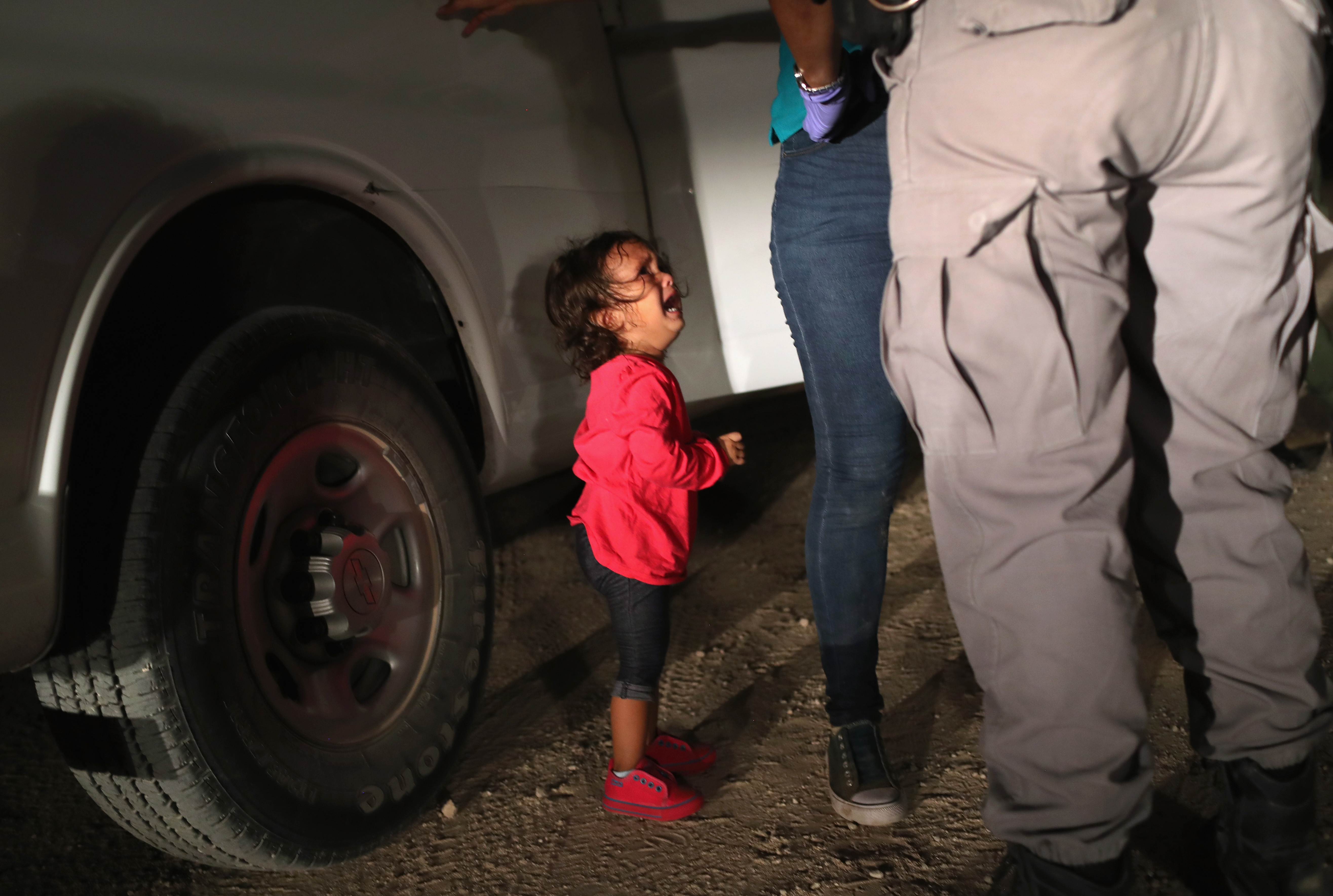A 2-year-old Honduran girl cries as an official searches her mother near the U.S.-Mexico border earlier this month in McAllen, Texas. For many, the image has become indelibly associated with a Trump administration policy that for weeks separated migrant children from their parents — but the girl's father says she was not separated from her mother.