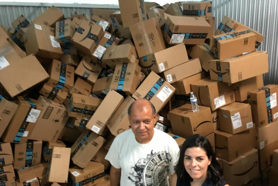 In this photograph taken June 24, 2018, Catholic Charities of the Rio Grande Valley staffer Eli Fernandez and volunteer Natalie Montelongo pose for a photo as they stand by a pile of unsorted Amazon boxes packed with donations in McAllen, Texas.