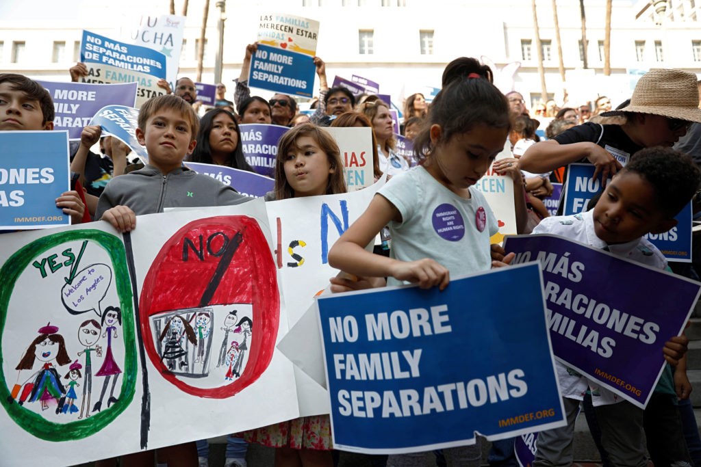 People hold signs to protest against U.S. President Donald Trump's executive order to detain children crossing the southern U.S. border and separating families outside of City Hall in Los Angeles, California, U.S. June 7, 2018.