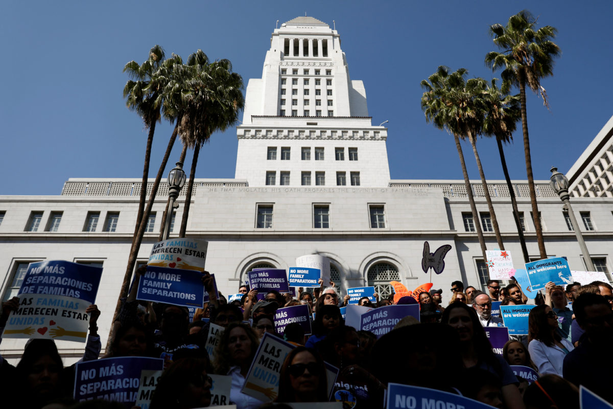 People hold signs to protest against President Donald Trump's executive order to detain children crossing the southern U.S. border and separating families outside of City Hall in Los Angeles, California.