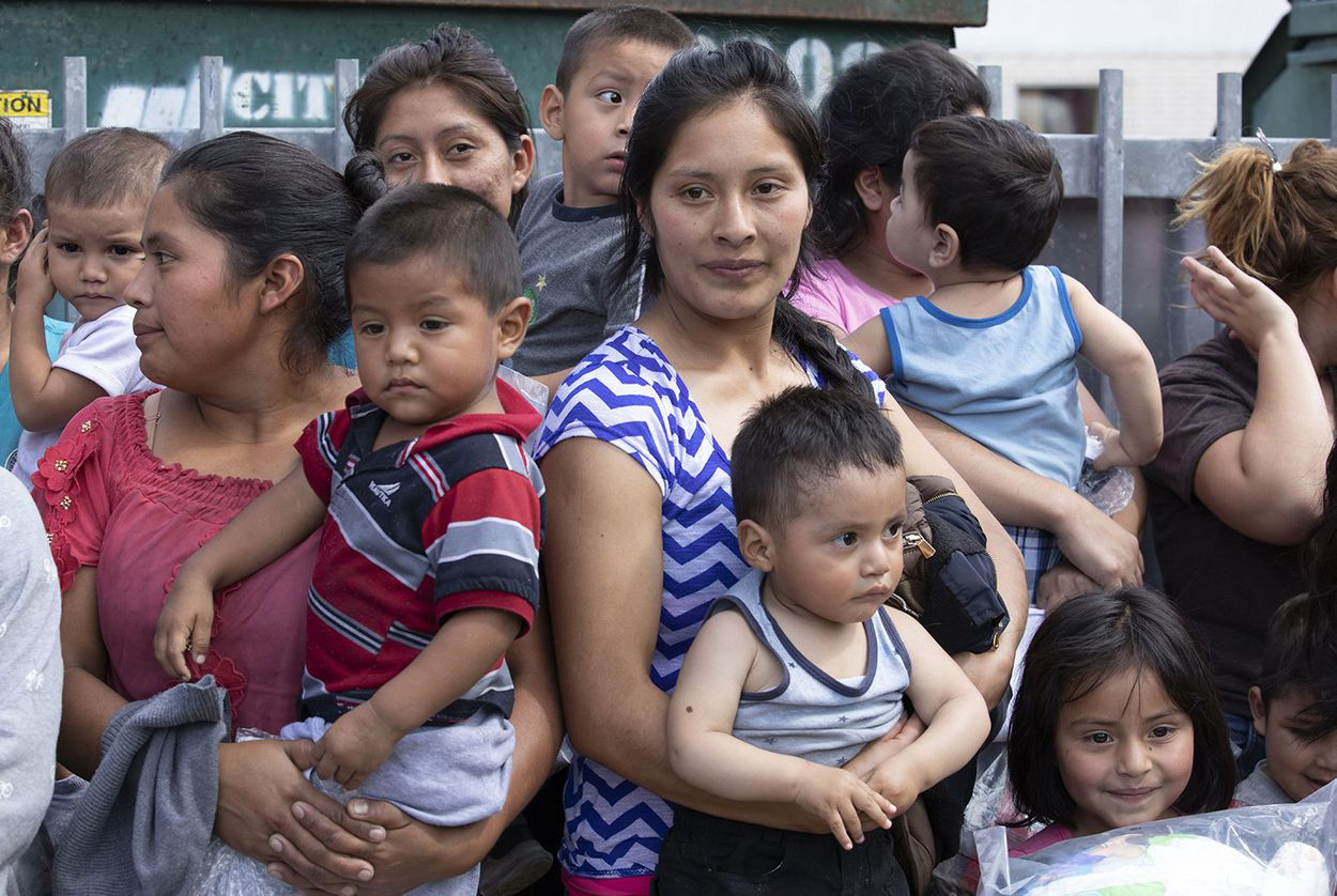 About 25 immigrant mothers and their children caught coming across the Texas-Mexico border are released at the McAllen bus station wearing ankle monitors on June 22, 2018.