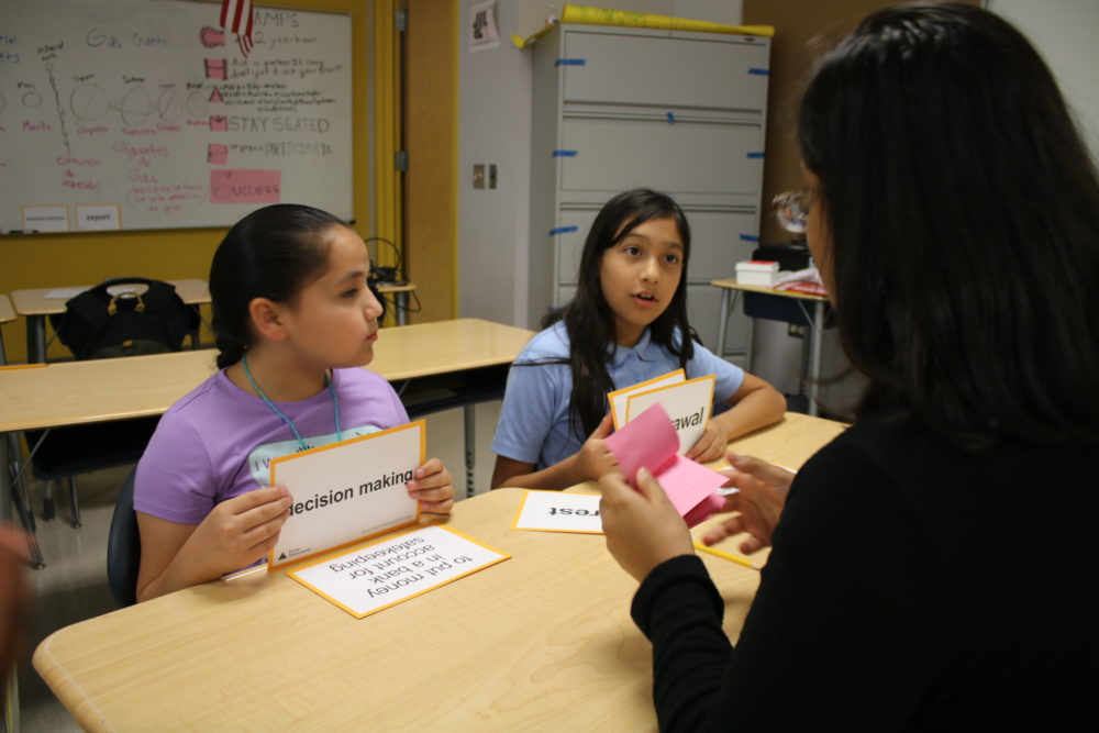 Volunteer Anusha Sood quizzes students Nallely Cedillo and Mariana Rosa on financial literacy.
