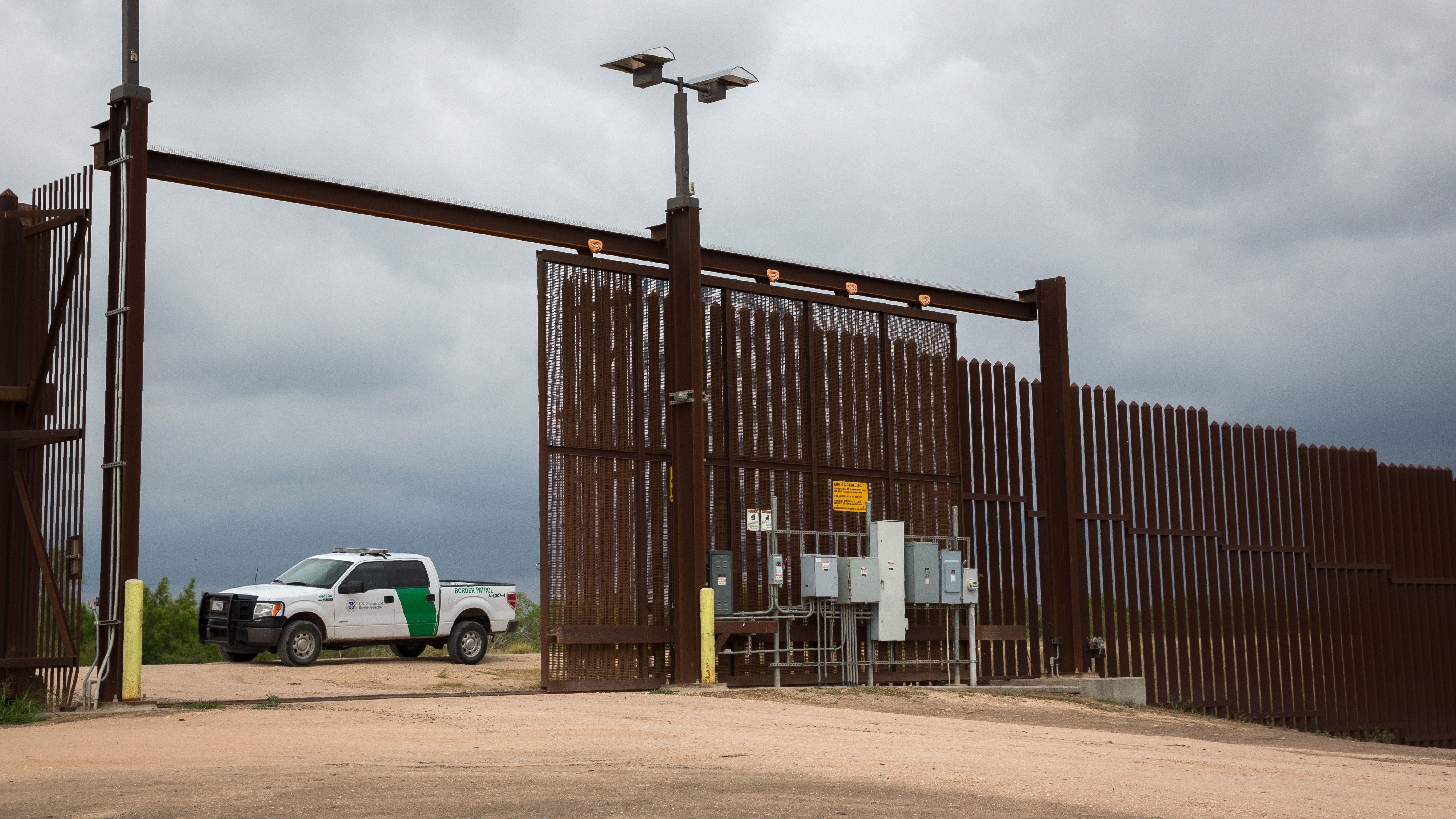 A U.S. Border Patrol agent keeps watch at a gate on the U.S.-Mexico border fence near San Benito, Texas.
