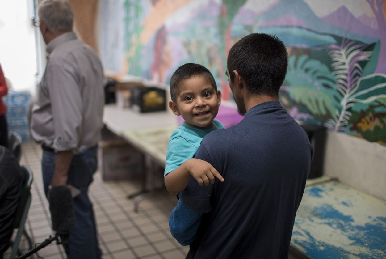 Pablo Ortiz and his 3-year-old Andres, both from Guatemala, walk into the common area of the Annunciation House in El Paso on Wednesday, July 11, 2018. Ortiz and his son were separated by ICE in April and were reunited and released late Tuesday night.