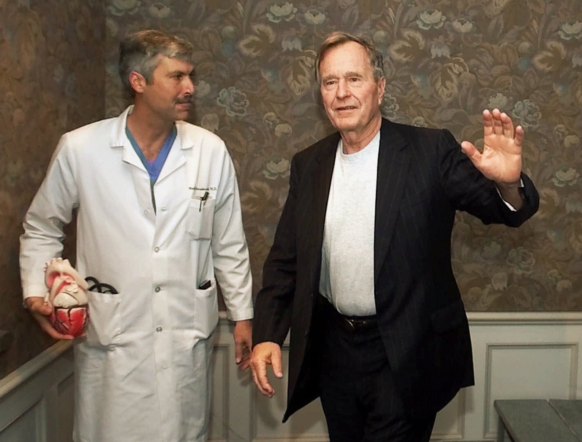 FILE - In this Feb. 25, 2000, file photo, former President George H.W. Bush waves as he leaves Methodist Hospital with his cardiologist, Mark Hausknecht, after a news conference in Houston. Hausknecht, who once treated former President George H.W. Bush, was fatally shot by a fellow bicyclist Friday, July 20, 2018, while riding through a Houston medical complex, and police were trying to determine if the shooting was random or a targeted act.
