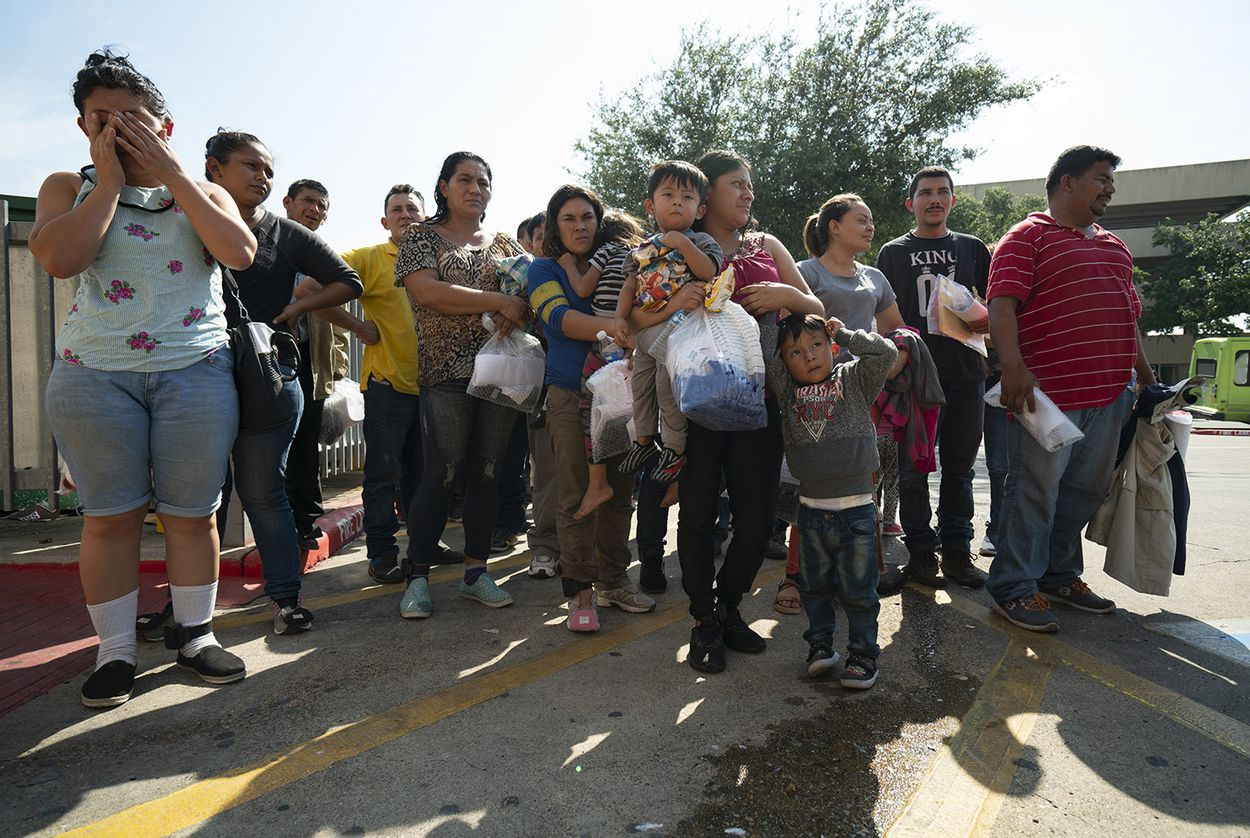 Immigrants, many wearing ankle monitors, are dropped off at the McAllen Central Station, where they are they are given bus tickets to other parts of the country. On Saturday, June 23, 2018.