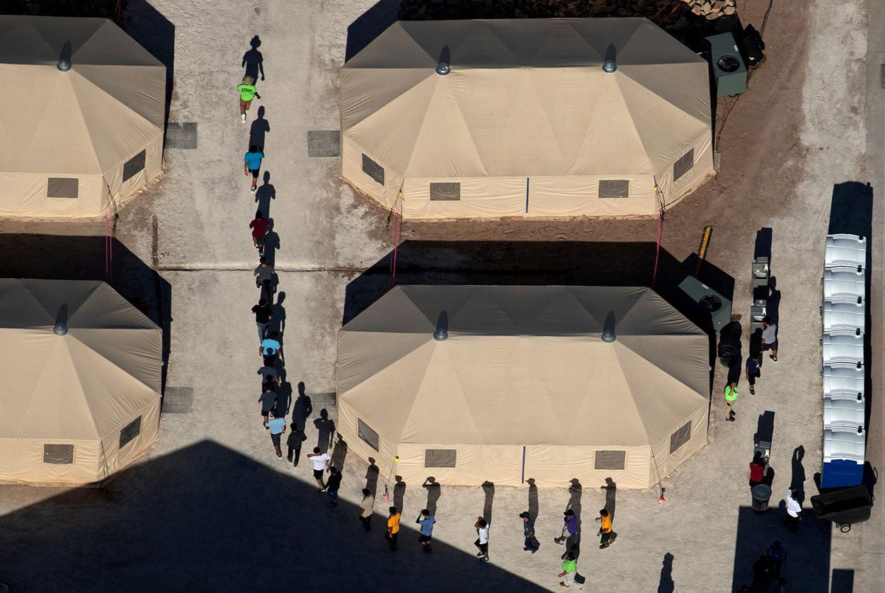 Immigrant children are led by staff in single file between tents at a detention facility next to the Mexican border in Tornillo on June 18, 2018.