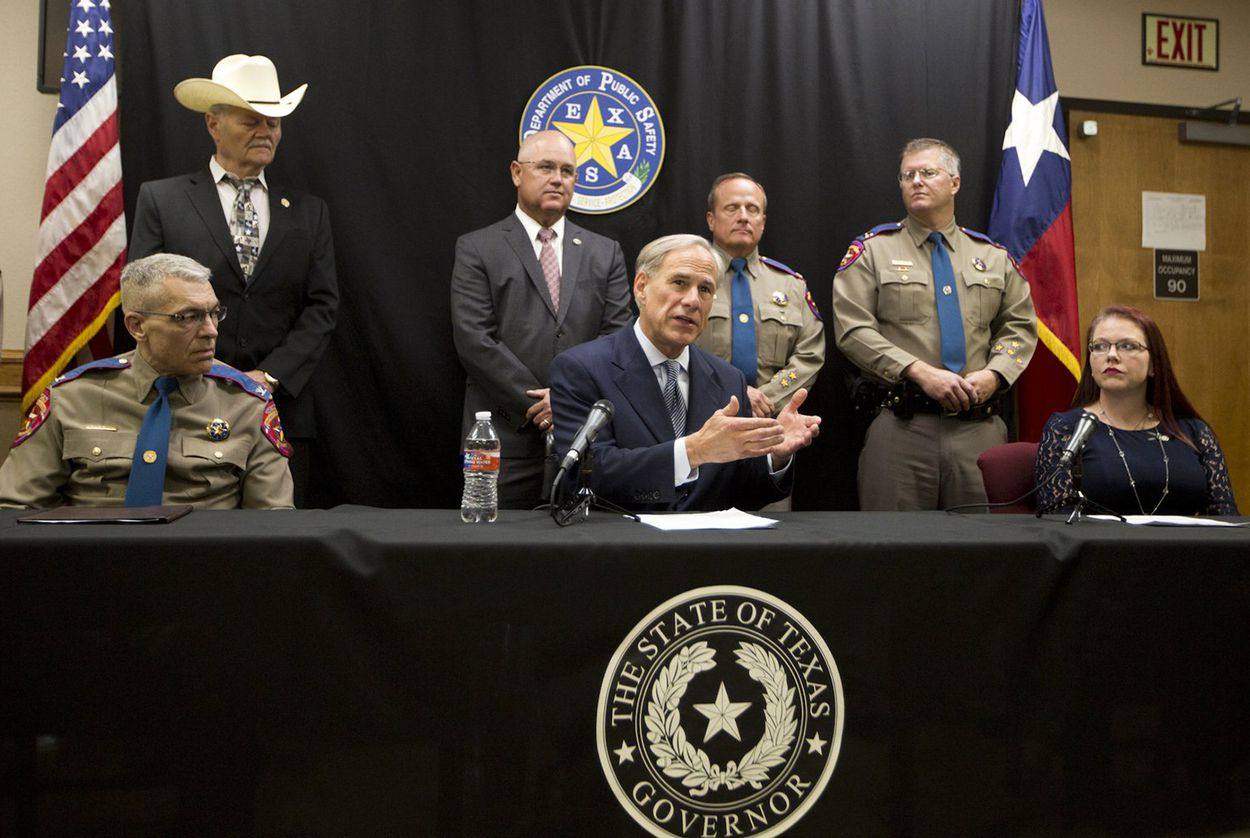 Gov. Greg Abbott. joined by DPS Director Steve McCraw (seated, left) and Kasey Allen, widow of Damon Allen, speaks at a press conference in Waco on August 7, 2018.