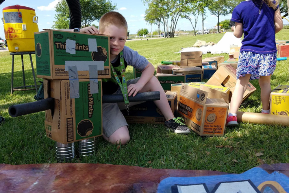 A boy and the robot he made from boxes