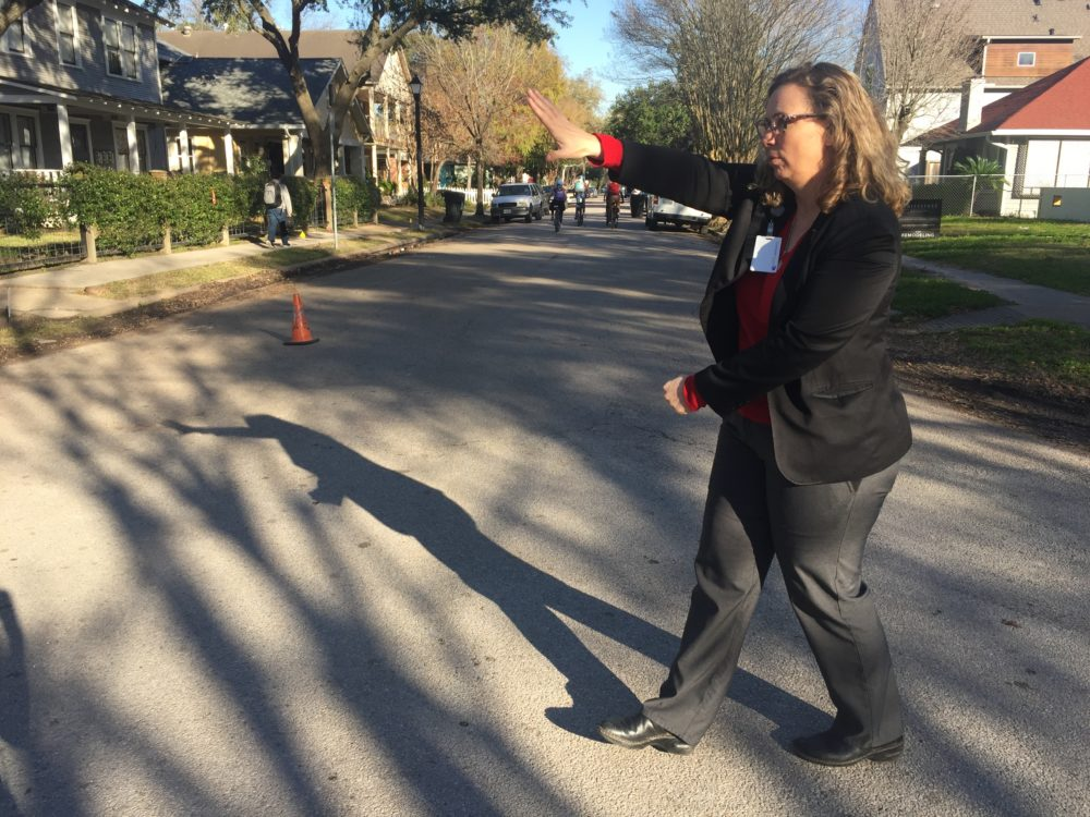 Principal Angela Sugarek directs traffic at an intersection near her school, Hogg Middle. She fills in as crossing guard because she doesn't have the budget to hire another one.