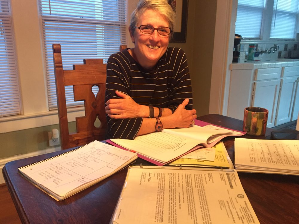 Homeowner and retired teacher Lisa Bidelspach says that she picks up substitute teaching to pay her property tax bill. She keeps binders and folders with notes to protest her appraisal at the county.