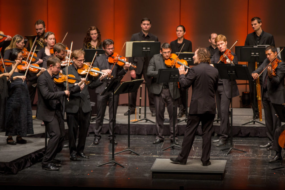 Concert photo of orchestra musicians and conductor