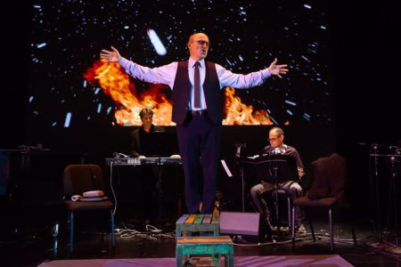 Performance photo of tenor with musicians in background.