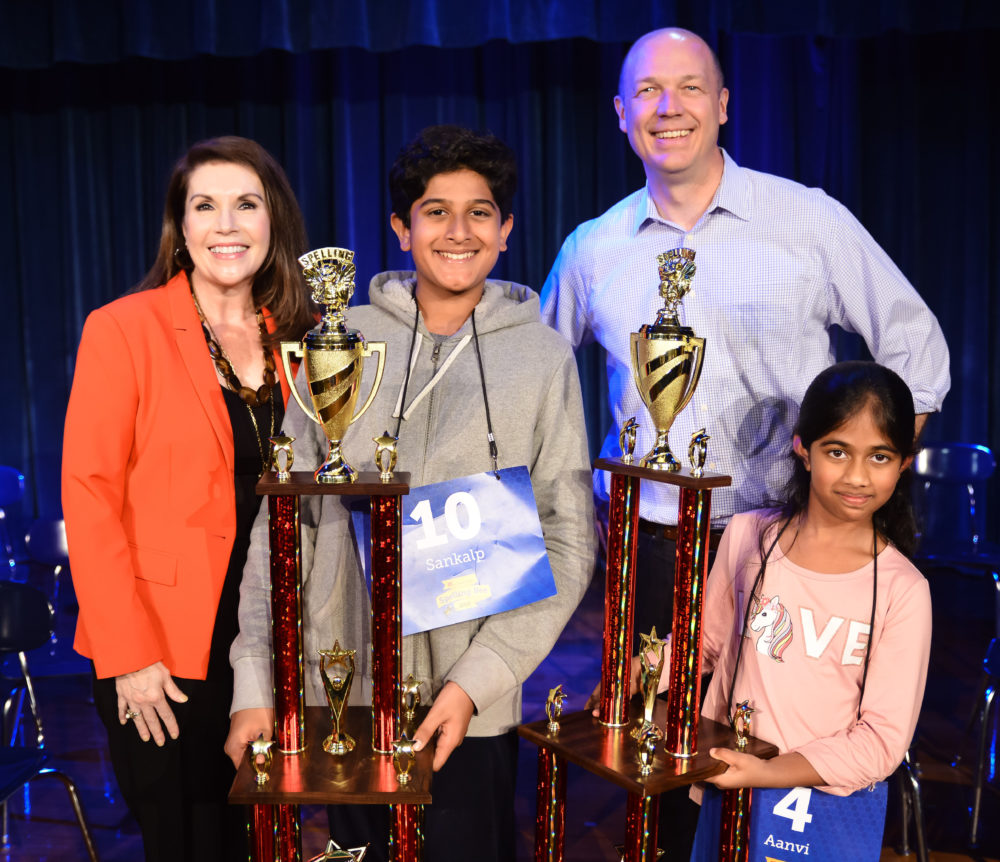 2019 HPM Spelling Bee winner Aanvi Manda (right) and runner-up Sankalp Gautam (left), with HPM's Vice-President and General Manager, Lisa Shumate, and Executive Director of Operations, Josh Adams.