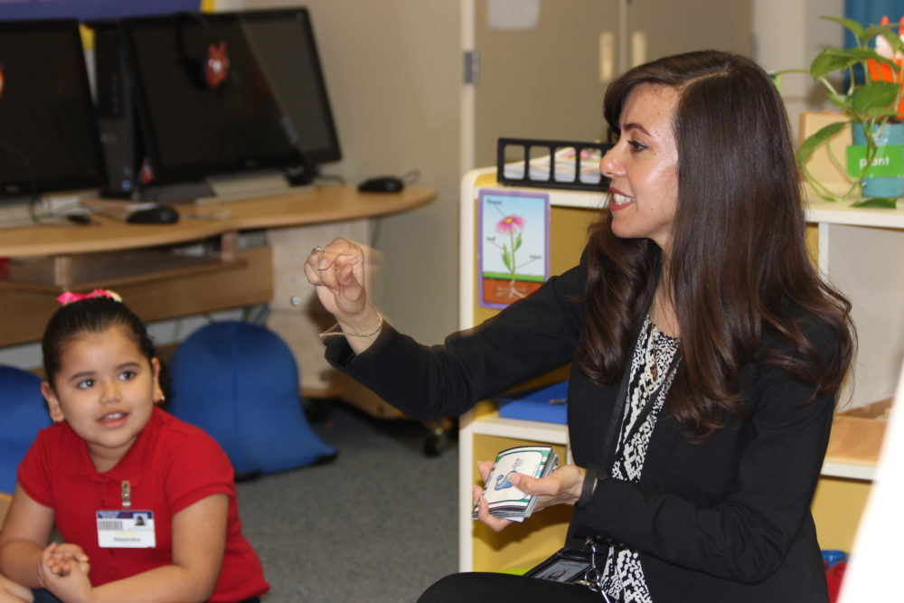 Bilingual pre-K teacher Atanea Raptis coaches her students on their letter sounds and numbers.