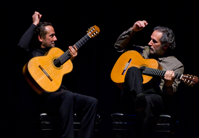 Concert photo of Sergio and Odair Assad performing on guitars