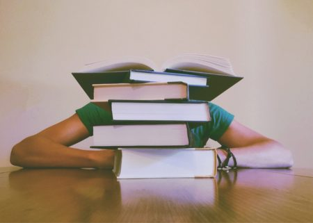 A Student Behind a Stack of Books