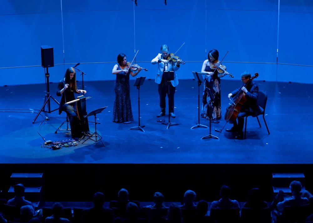 Photo of a string quartet and theremin player on stage