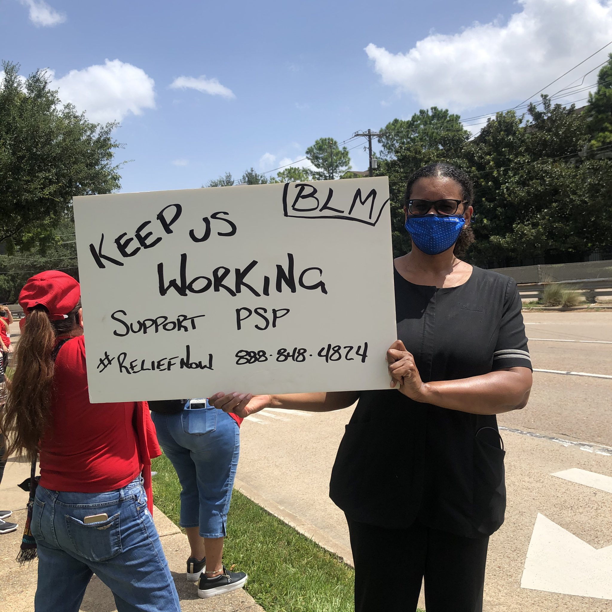 An airline worker holds a sign outside of Sen. John Cornyn's office.