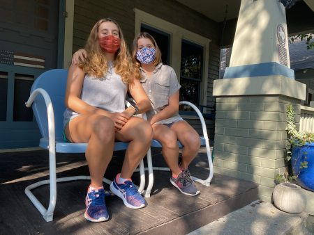 Lily and Piper Jordan wear masks and sit on their front porch. They've spent the last five weeks doing virtual school at home.