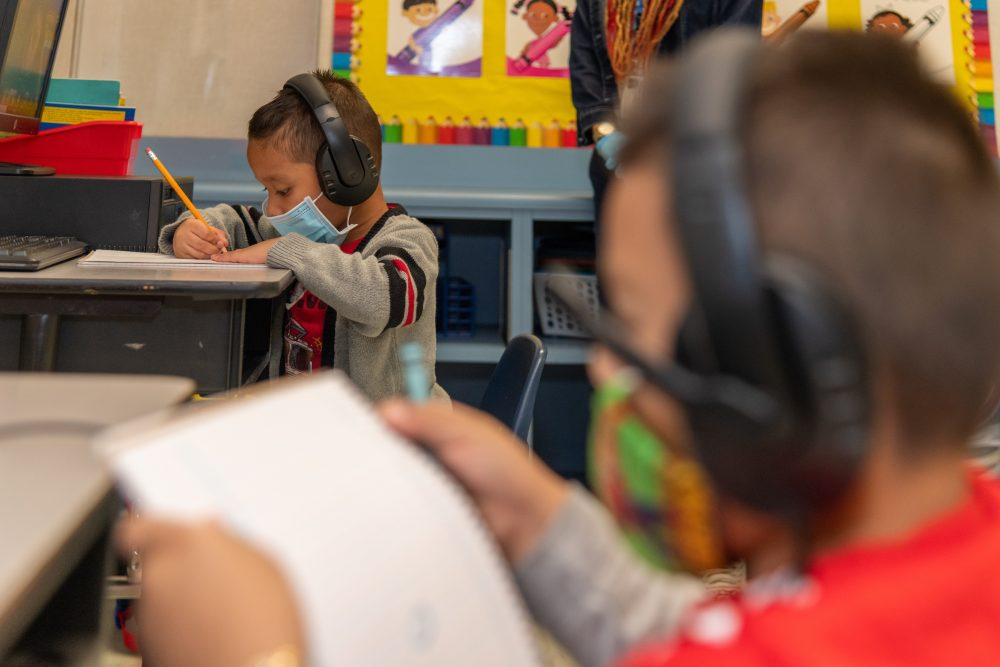 Two elementary-age boys study while wearing maskes and headphones.