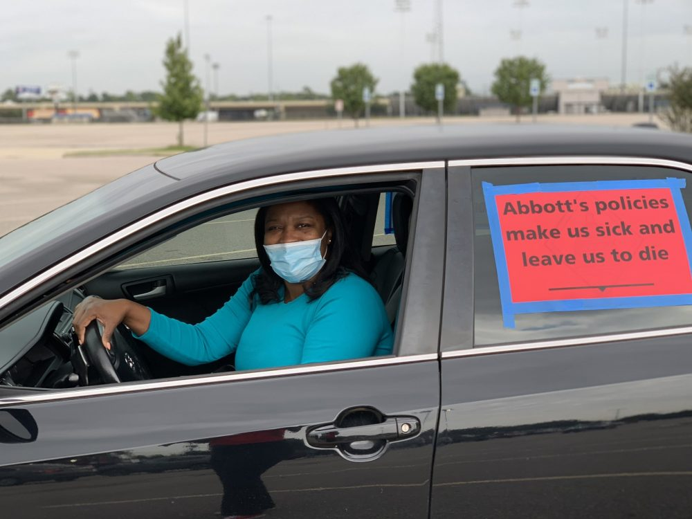 "An educator wears a mask and sits in her car with a sign on the window that says ""Abbott's policies make us sick and leave us to die."""