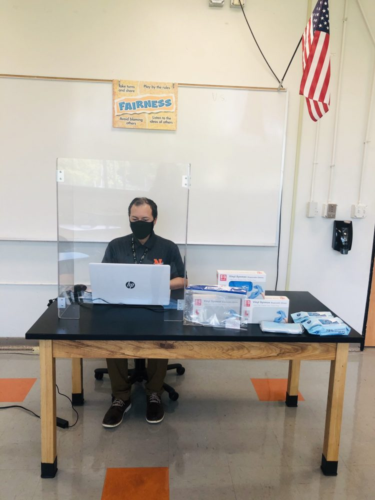 Teacher Daniel Santos sits at his desk behind a face shield and wears a box. He has lots of cleaning wipes and extra gloves and masks on his desk for students who need them.