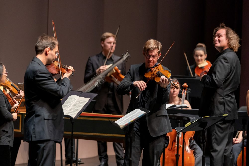 Photo of two violinists and orchestra