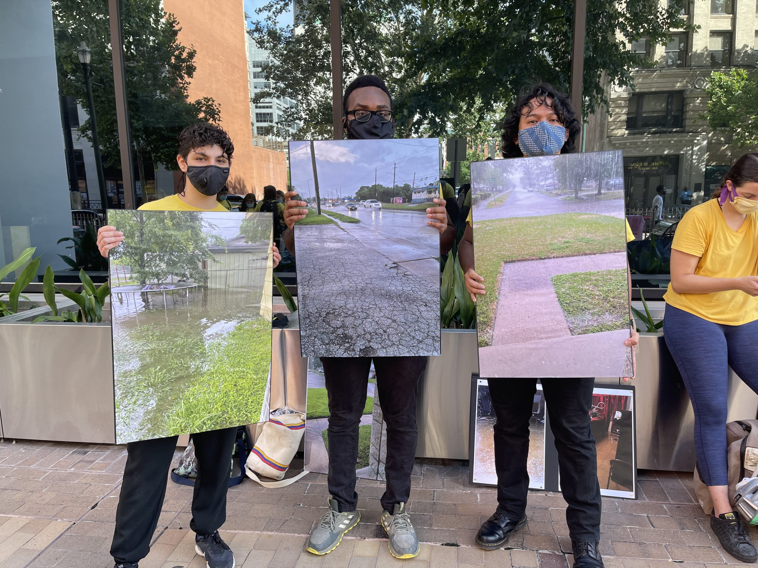 Members of the Northeast Action Collective rally at Harris County Commissioners Court, carrying photos of prior flood damage.